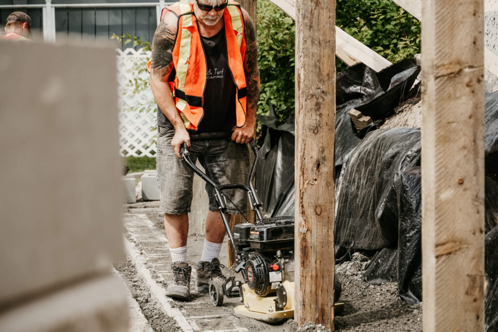 An Earth and Turf Landscaping Edmonton worker pushing a piece of retaining wall -related machinery near a wooden post.