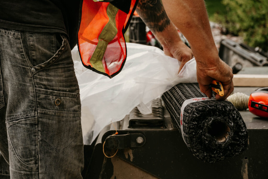 Close-up of an Earth and Turf Landscaping Edmonton worker unpacking a roll of wire mesh on a retaining wall job site.